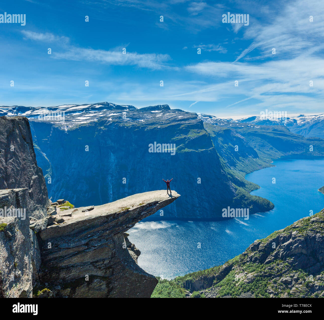 The summer view of Trolltunga (famous The Troll's tongue Norvegian destination) and Ringedalsvatnet lake in Odda, Roldal, Norway. Man tourist on rock. - Stock Image