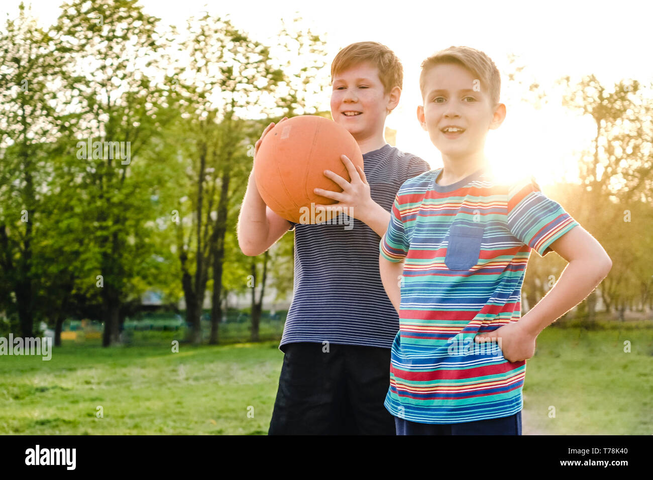 Two happy young boy friends or brothers standing on a rural sports field holding up a basketball with happy grins backlit by the glow of the setting s - Stock Image