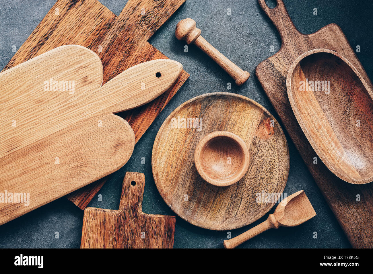 Set of wooden kitchen utensils, cutting boards, bowl, plate, mortar and pestle, scoop. Flat lay, top view - Stock Image