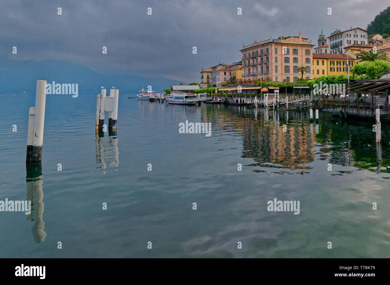 A view across the harbour to the Hotel Metropole and other colourful buildings of Bellagio, with reflections in the water of Lake Como - Stock Image