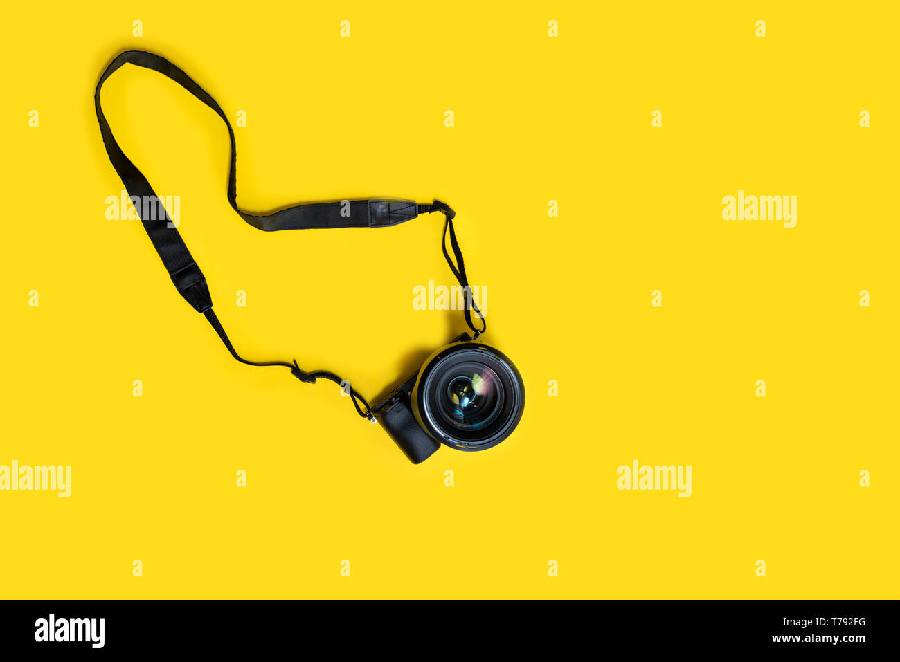 Mirrorless black camera on yellow background, summer memmories photograher - Stock Image