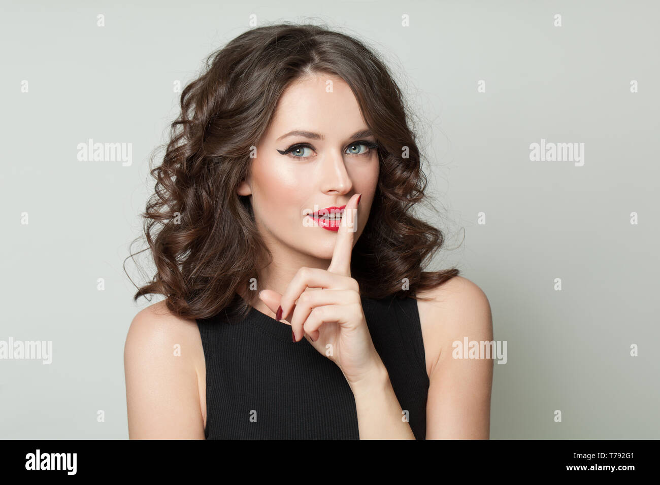 Pretty woman showing a sign of silence. Shh! Womens secrets. - Stock Image