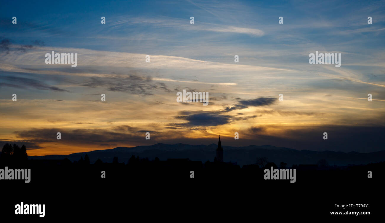 colorful sunset with different types of clouds and a hill and valley silhouette with a church tower in the austrian alps in styria - Stock Image