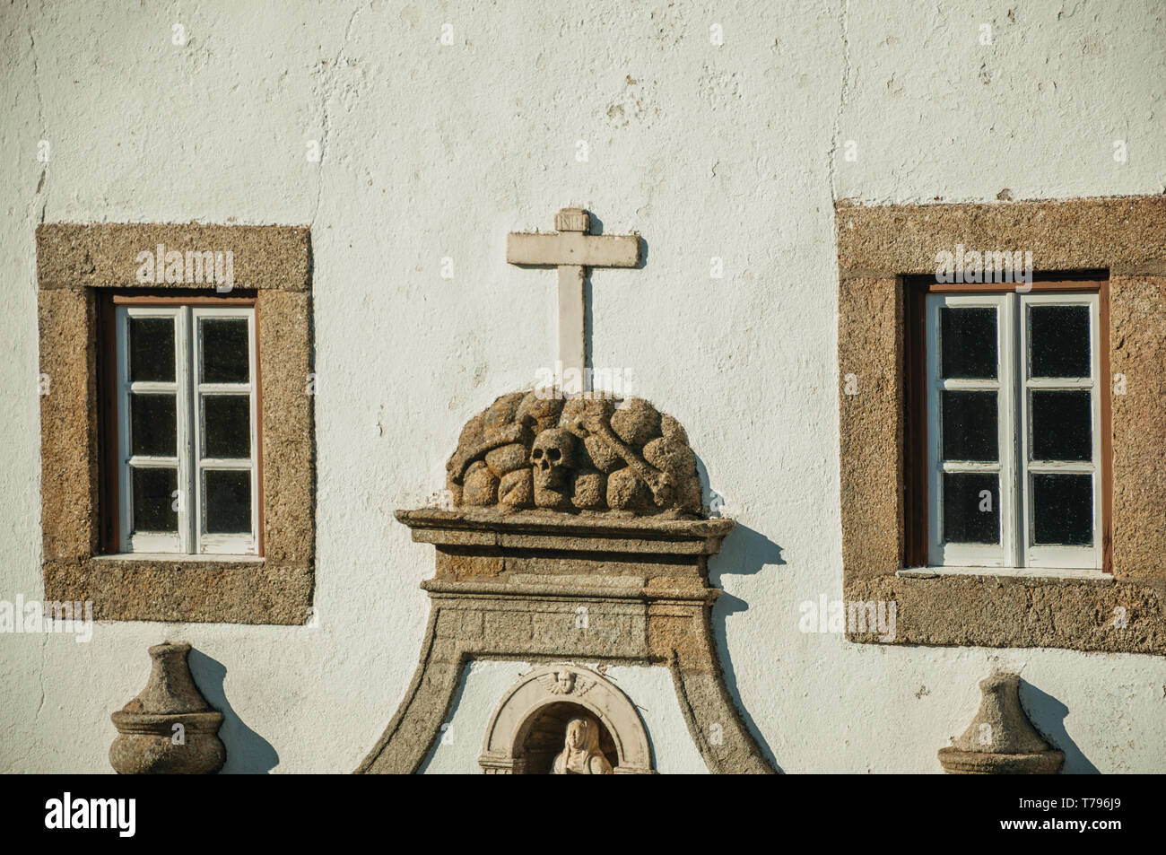 Skulls and cross carved in stone between windows embellishing the facade of church at Marvao. A medieval hamlet perched on a crag in Portugal. Stock Photo