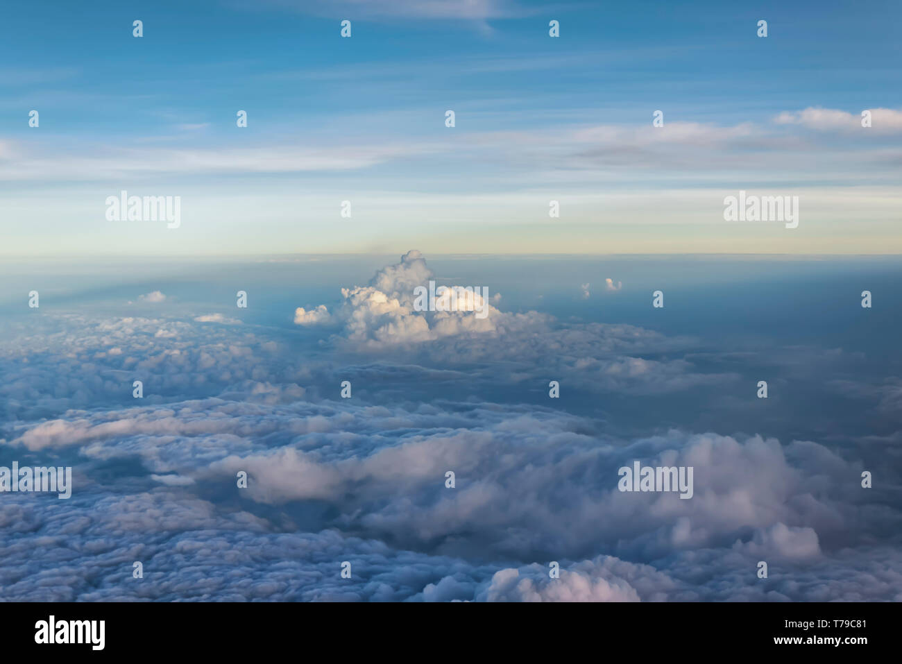 Aerial view of grey, billowy monsoon clouds hanging over the plains of India. Rain clouds--Cumulonimbus and Cumulus clouds are visible in the frame. - Stock Image