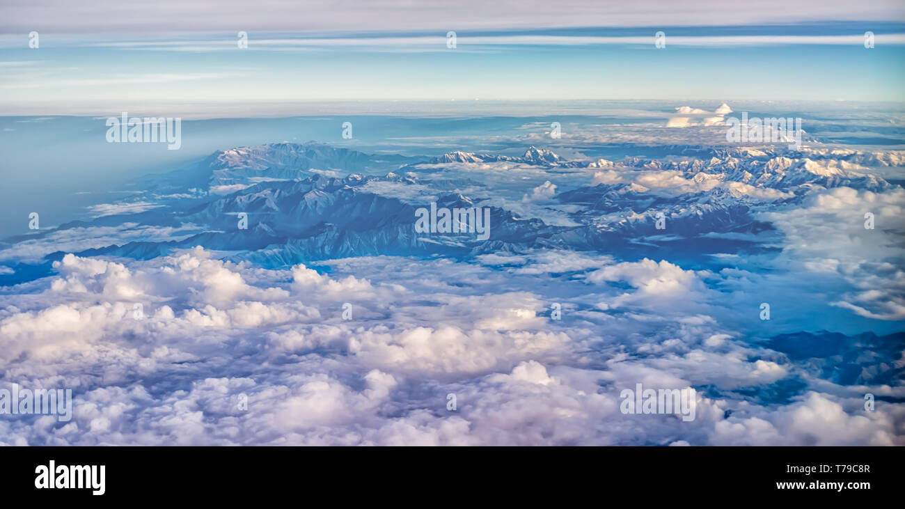 Aerial view of monsoon clouds over the mountain ranges of India. The snow covered peaks of the Dhauladhar/White range can be seen in the frame. - Stock Image