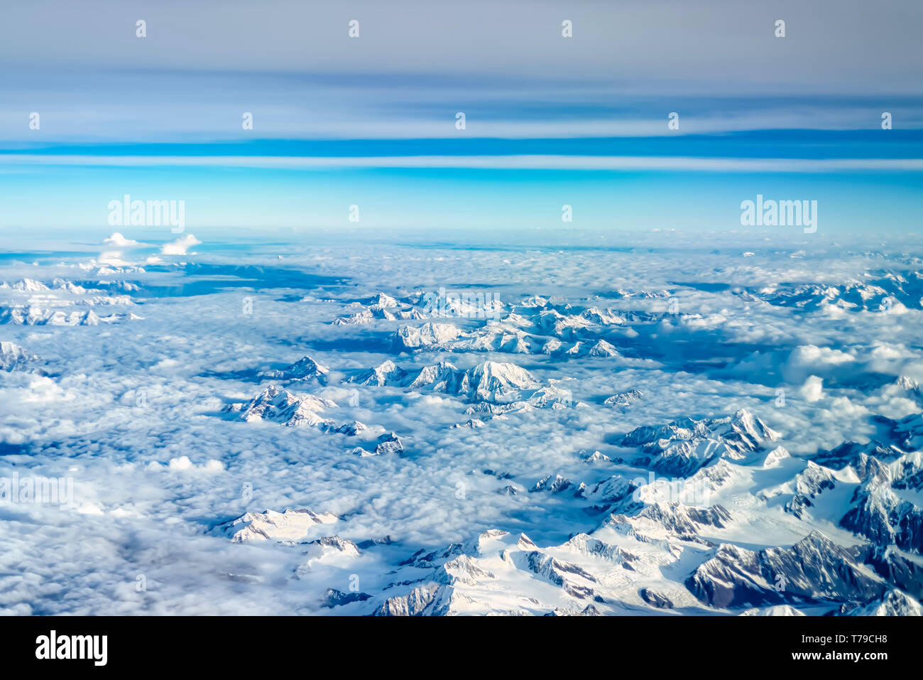 The snow covered peaks of the Dhauladhar/White range of the lesser Himalayas, India, poking out into the sky through layers of monsoon clouds. - Stock Image