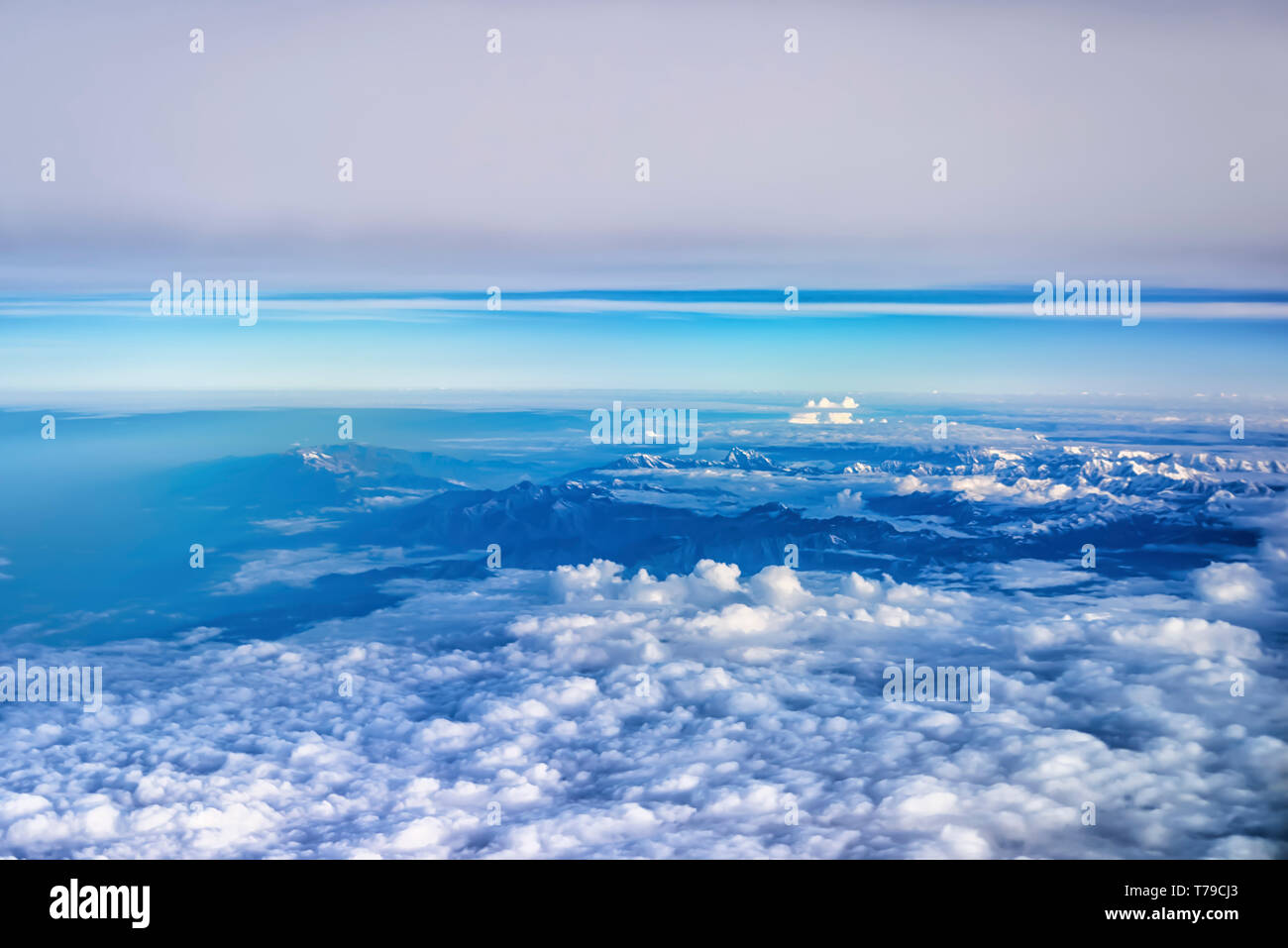 Aerial view of monsoon clouds over a mountain range in India. The snow covered peaks of Shivalik/Dhauladhar range can be seen on top right. - Stock Image