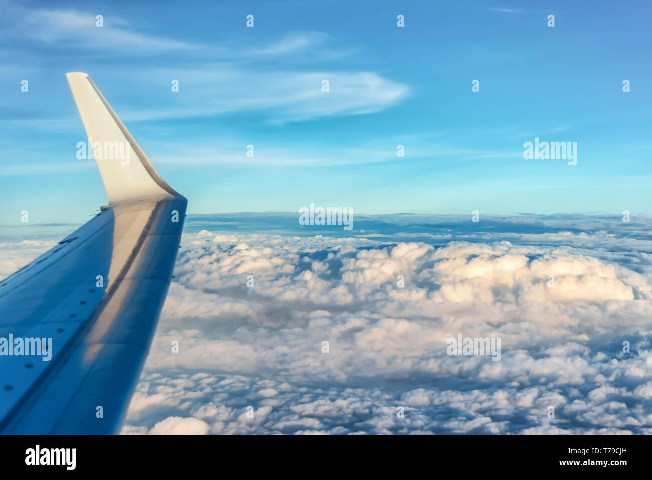 Aerial view of monsoon clouds over India. Cumulonimbus and Cumulus clouds are visible. Wing of the plane used as a foreground element. - Stock Image