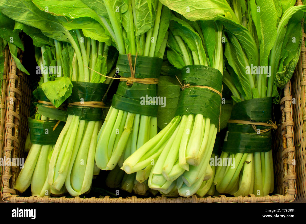 Close up picture of some celery (vegetable) wrapped and bundled in banana leaves. This is an excellent solution to replace plastic packaging and reduc - Stock Image