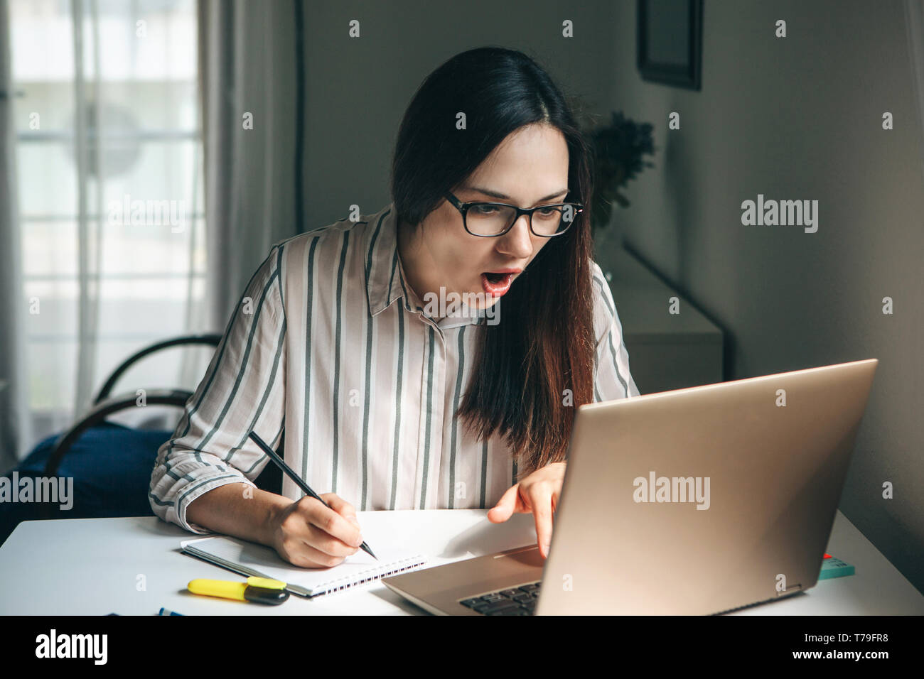 A young beautiful student girl does homework or works in a home office. She is surprised by the news or she has found an unexpected solution. Stock Photo