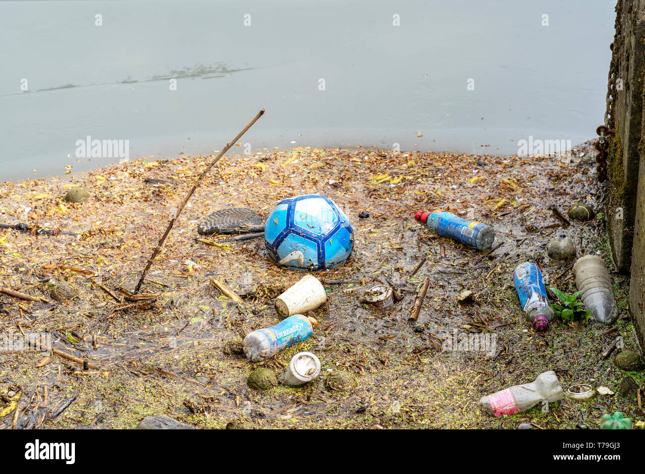 Plastic bottles and football in river - Stock Image