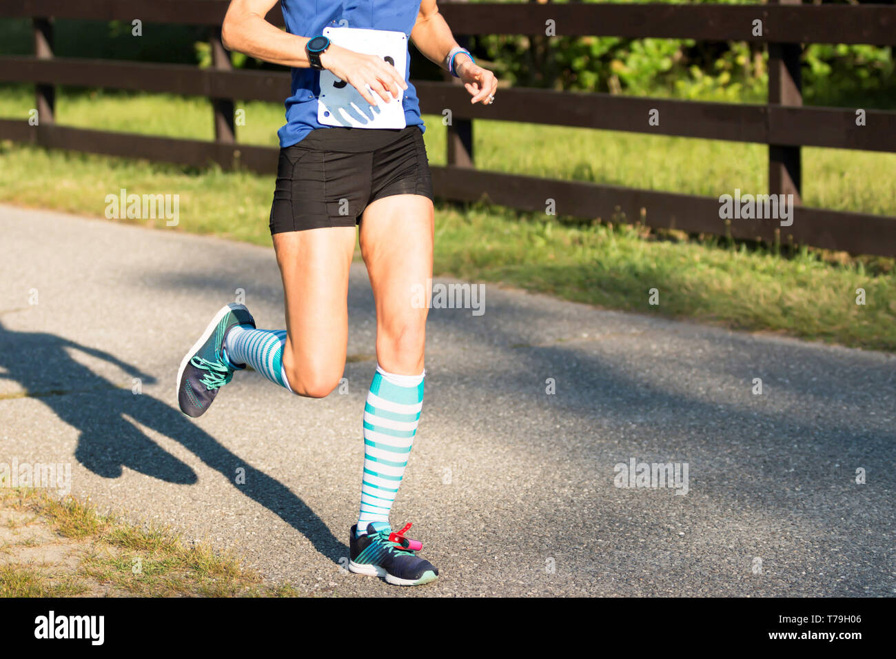 A women running the summer series in Belmont lake state park new york on a sunny afternoon - Stock Image