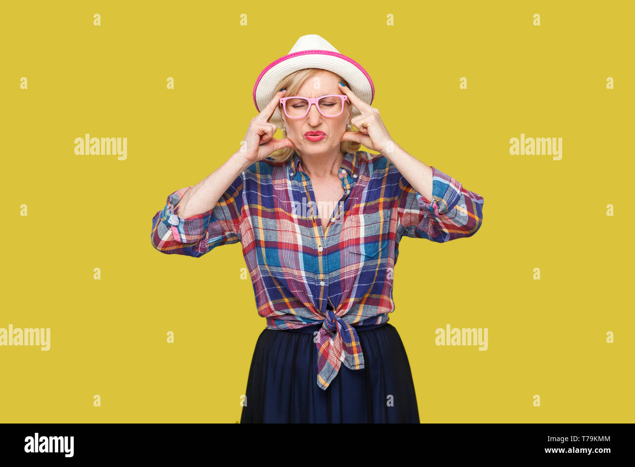 Headache or confusion. Portrait of frowning stylish mature woman in casual style with hat and eyeglasses standing holding her head with head pain. ind - Stock Image