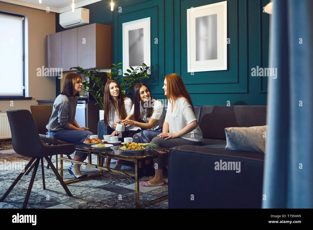 Young women having tea party at home  Stock Photo