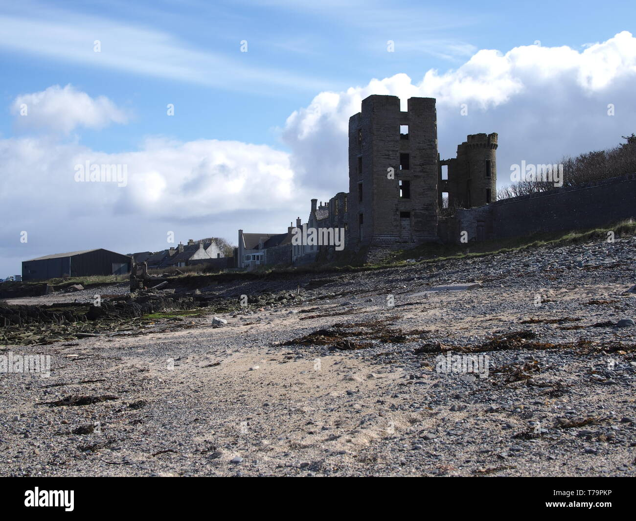 View of Thurso Castle ruin from the foreshore towards farm building in the background. - Stock Image