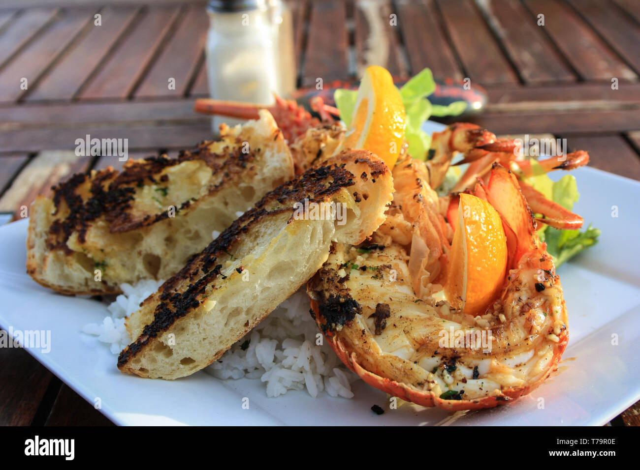 Close-up of a grilled lobster on a plate with rice, salat, orange and some french bread, North Island, New Zealand - Stock Image