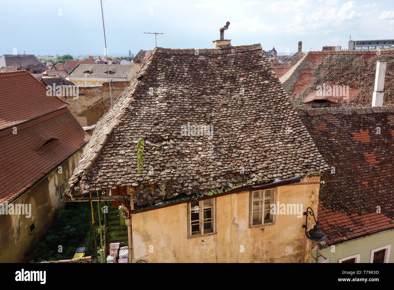Weathered rooftop of an old house with an unique chimney in Sibiu (Hermannstadt), Romania - Stock Image