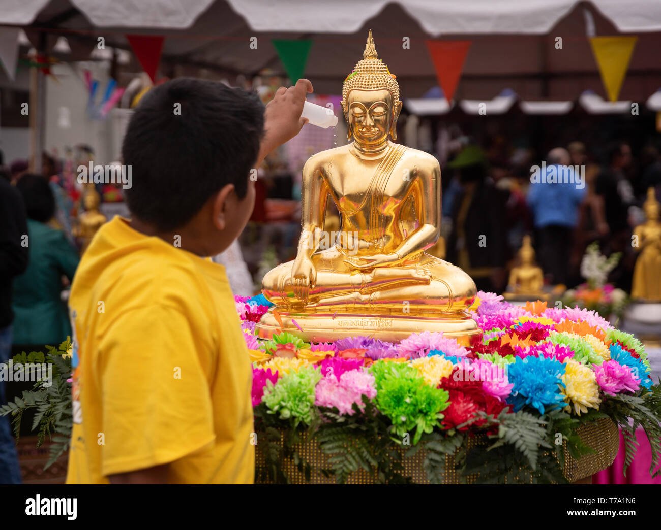 Sprinkling flower-scented water over Buddhist statue during Songkran Festival celebrating the Thai New Year, in Los Angeles, California. Stock Photo