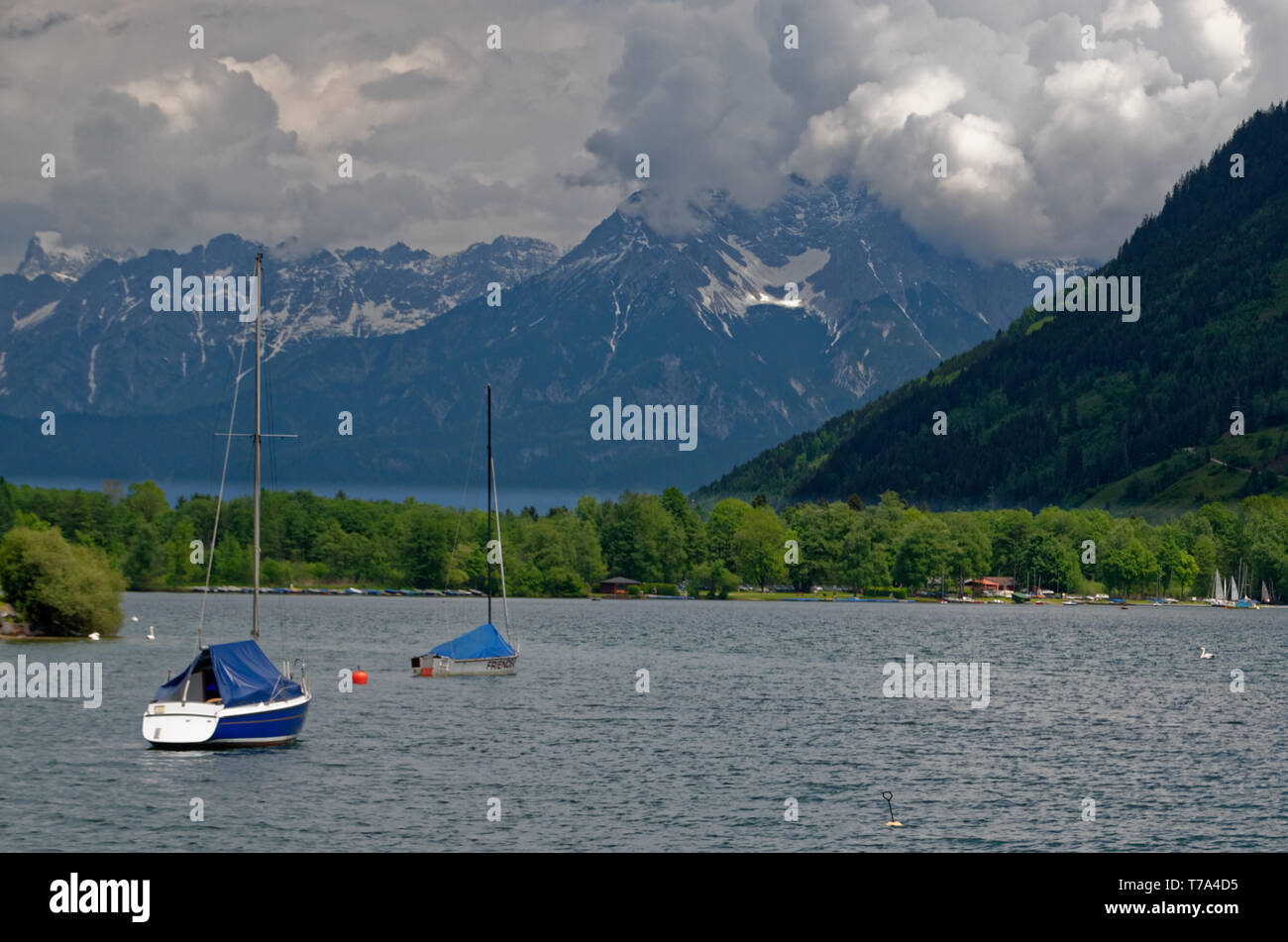 Anchored sailing boats on Zeller See (Lake Zell) pointing towards the mountains opposite Zell am See in Austria - Stock Image