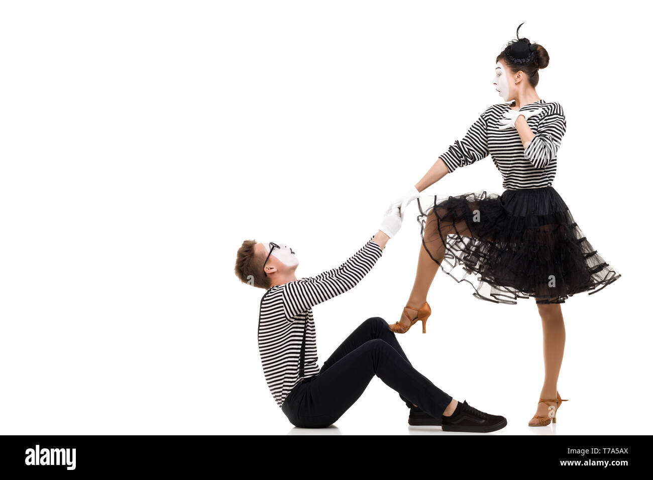Smiling mimes in striped shirts. Man and woman dressed as actors of pantomime theater isolated on white background - Stock Image