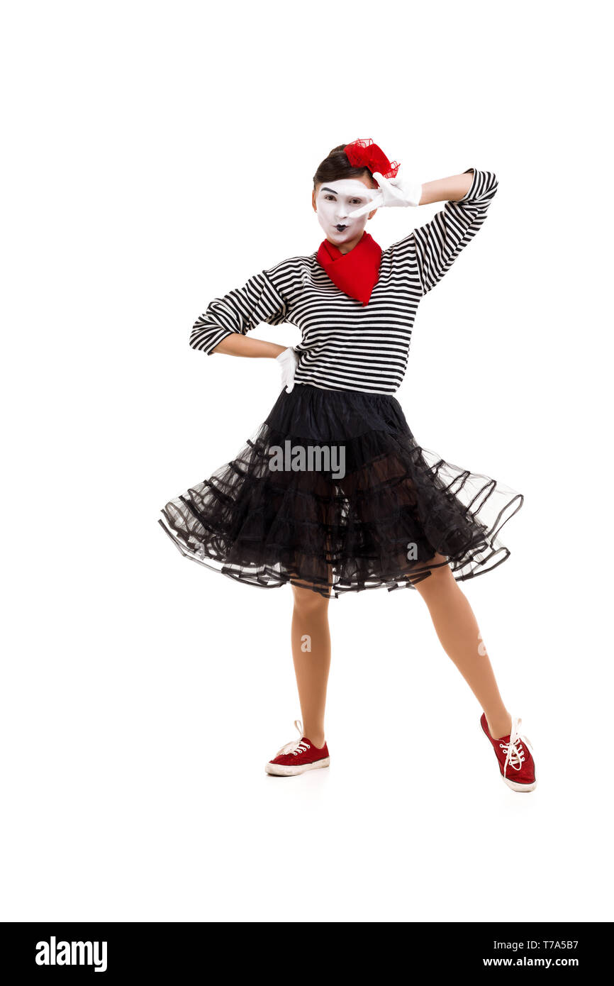 Full length portrait of a mime woman artist looking at camera and showing victory gesture isolated on white background - Stock Image