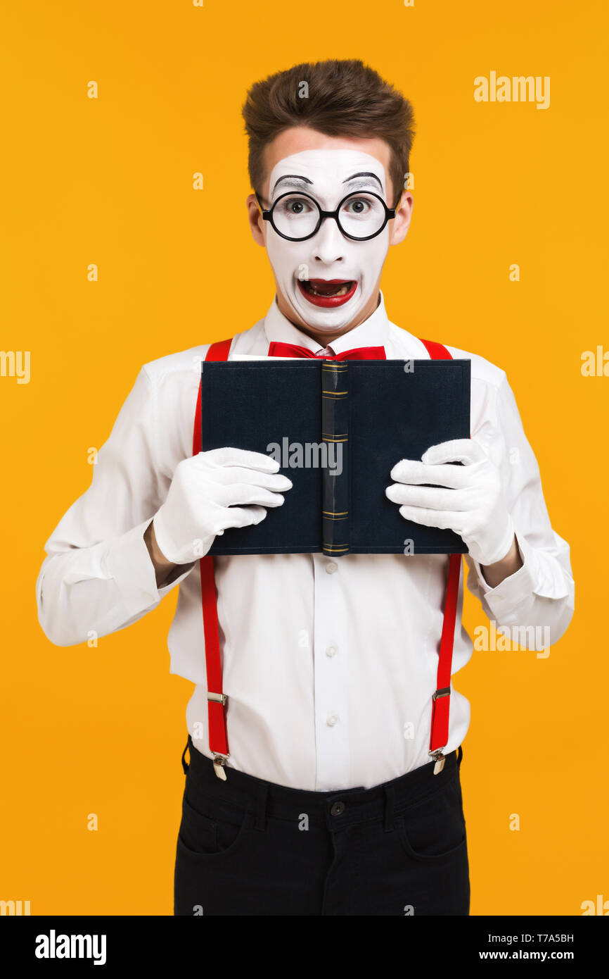 portrait of surprised mime man artist reading book isolated on yellow background - Stock Image