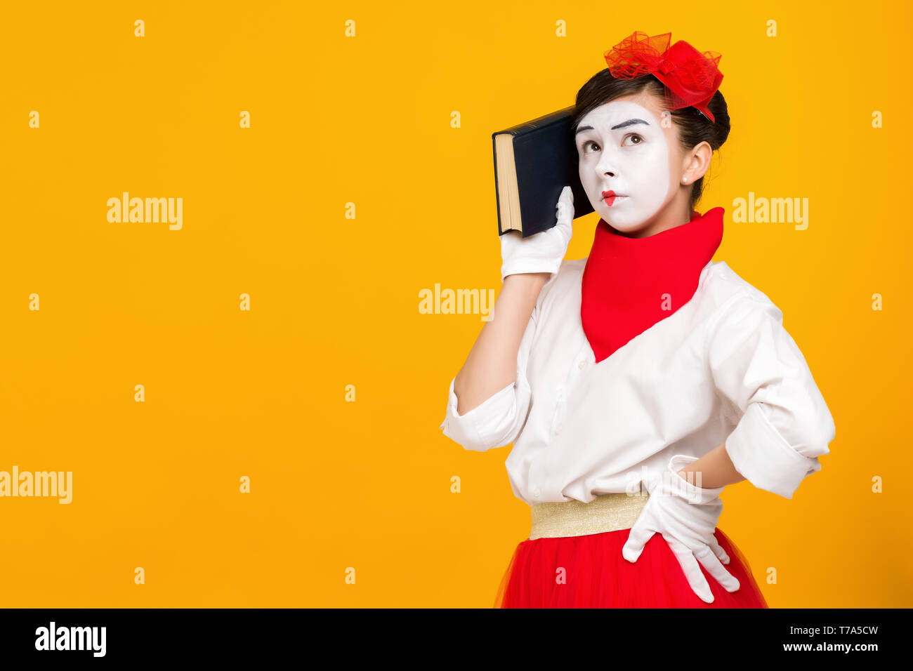 portrait of mime woman artist reading book isolated on yellow background . space for text - Stock Image