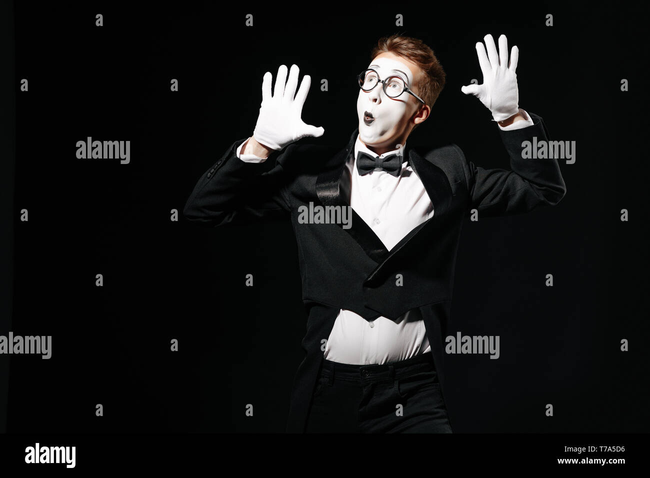 portrait of mime man holding his hands on an invisible wall on black background - Stock Image