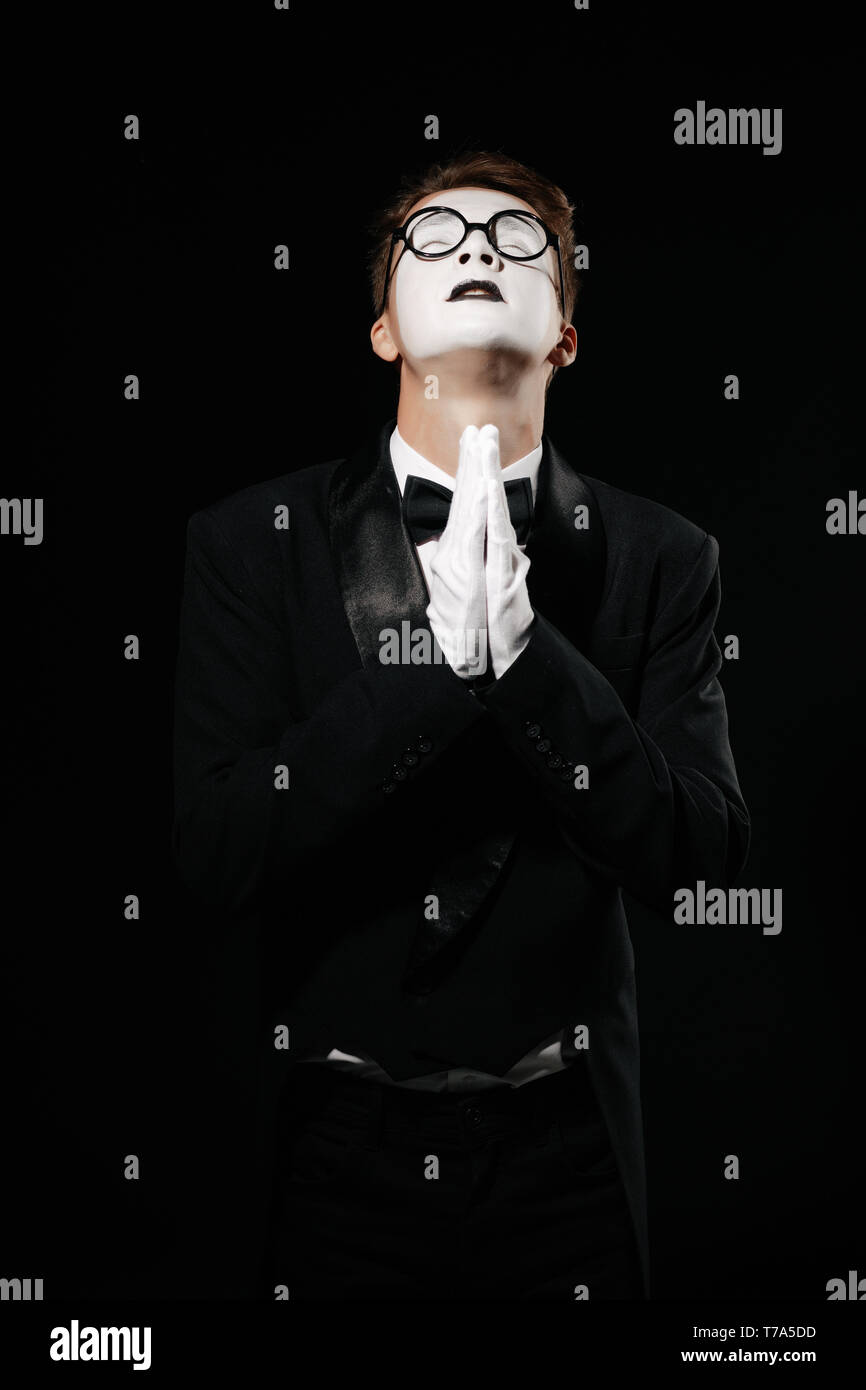 portrait of mime man in tuxedo and glasses praying on black background - Stock Image
