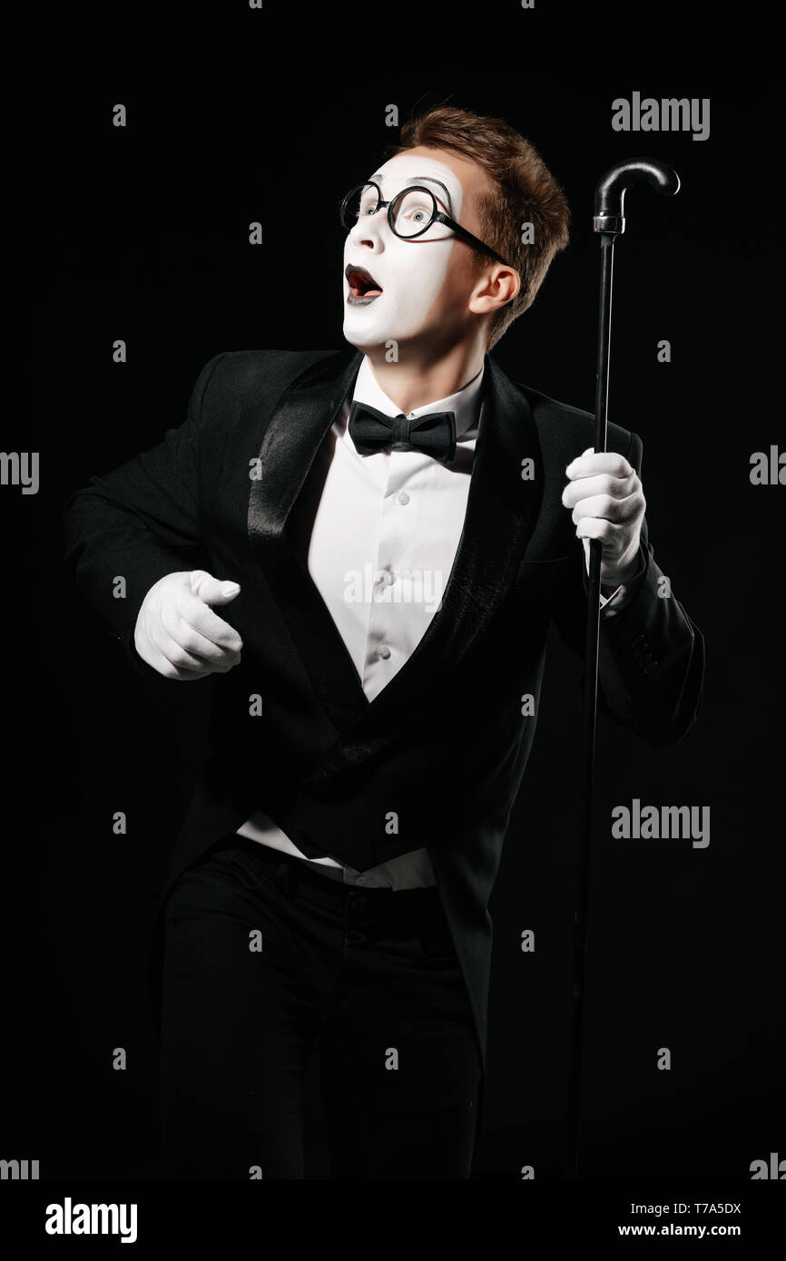 surprised mime man in tuxedo and glasses posing with walking stick on black background - Stock Image
