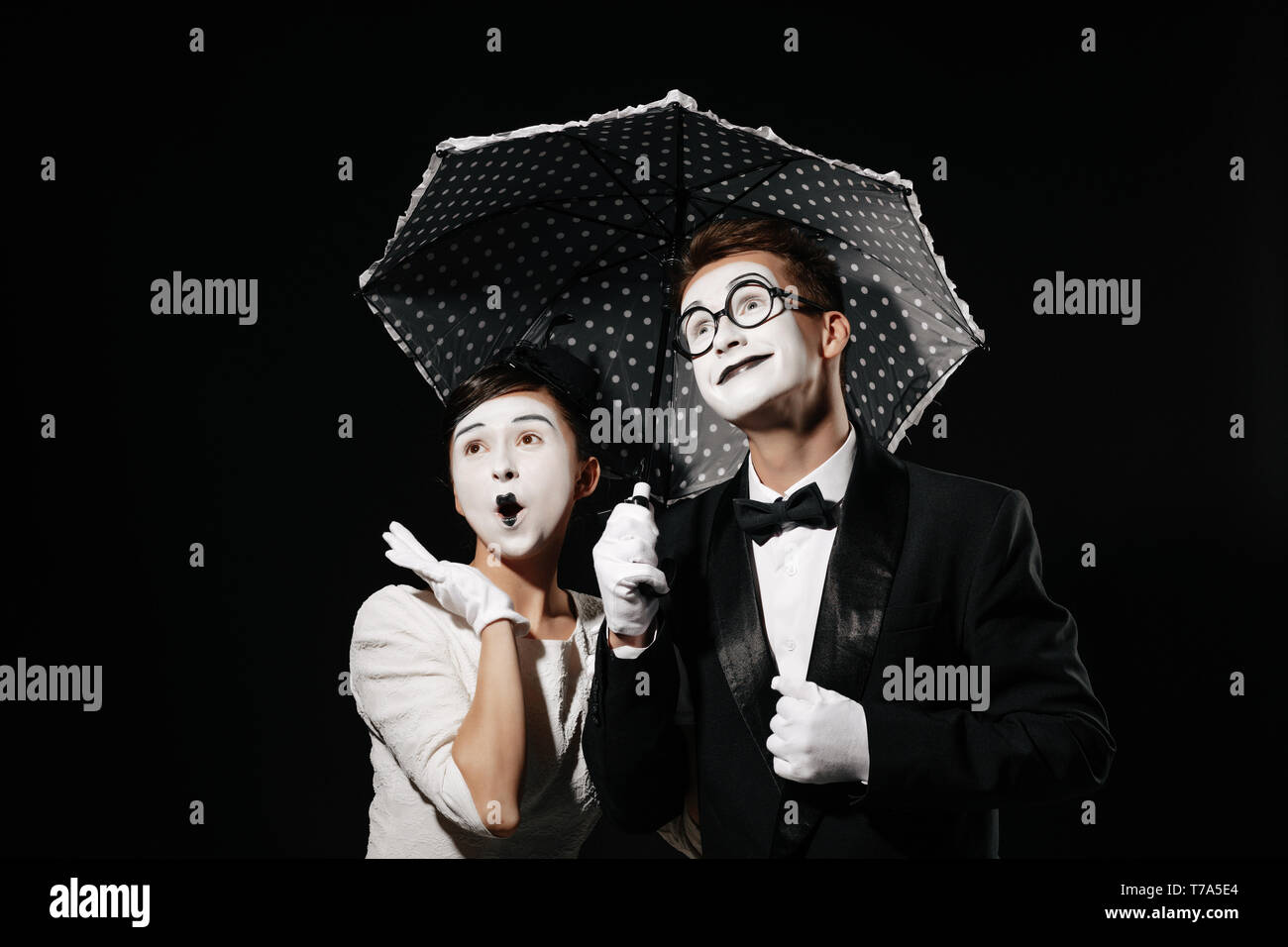 portrait of surprised couple mime with umbrella on black background. man in tuxedo and glasses and woman in white dress - Stock Image