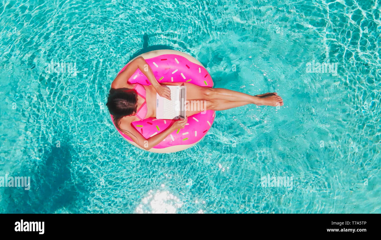 Young Woman Swims In The Sea In A Swimming Circle. Girl Resting In The Pool