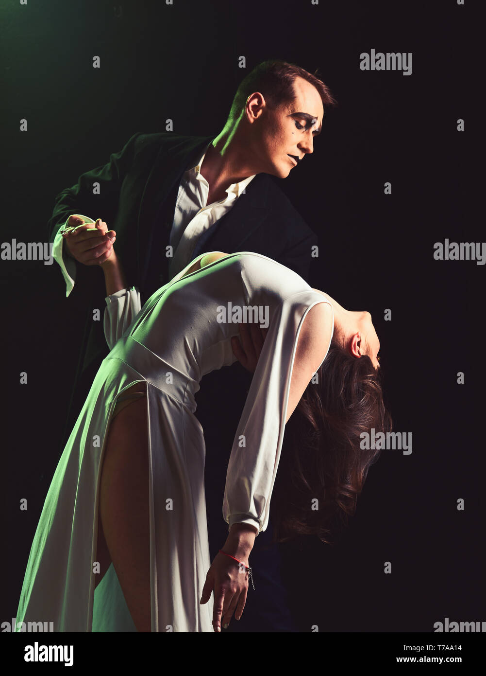 More than a little romance. Theatre actors miming through body motions. Couple of mime artists perform romance on stage. Couple in love with mime - Stock Image