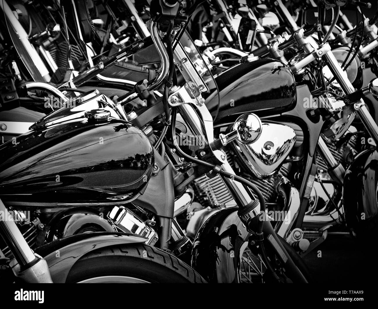Black and white photograph of similar style motorcycles parked side by side. - Stock Image