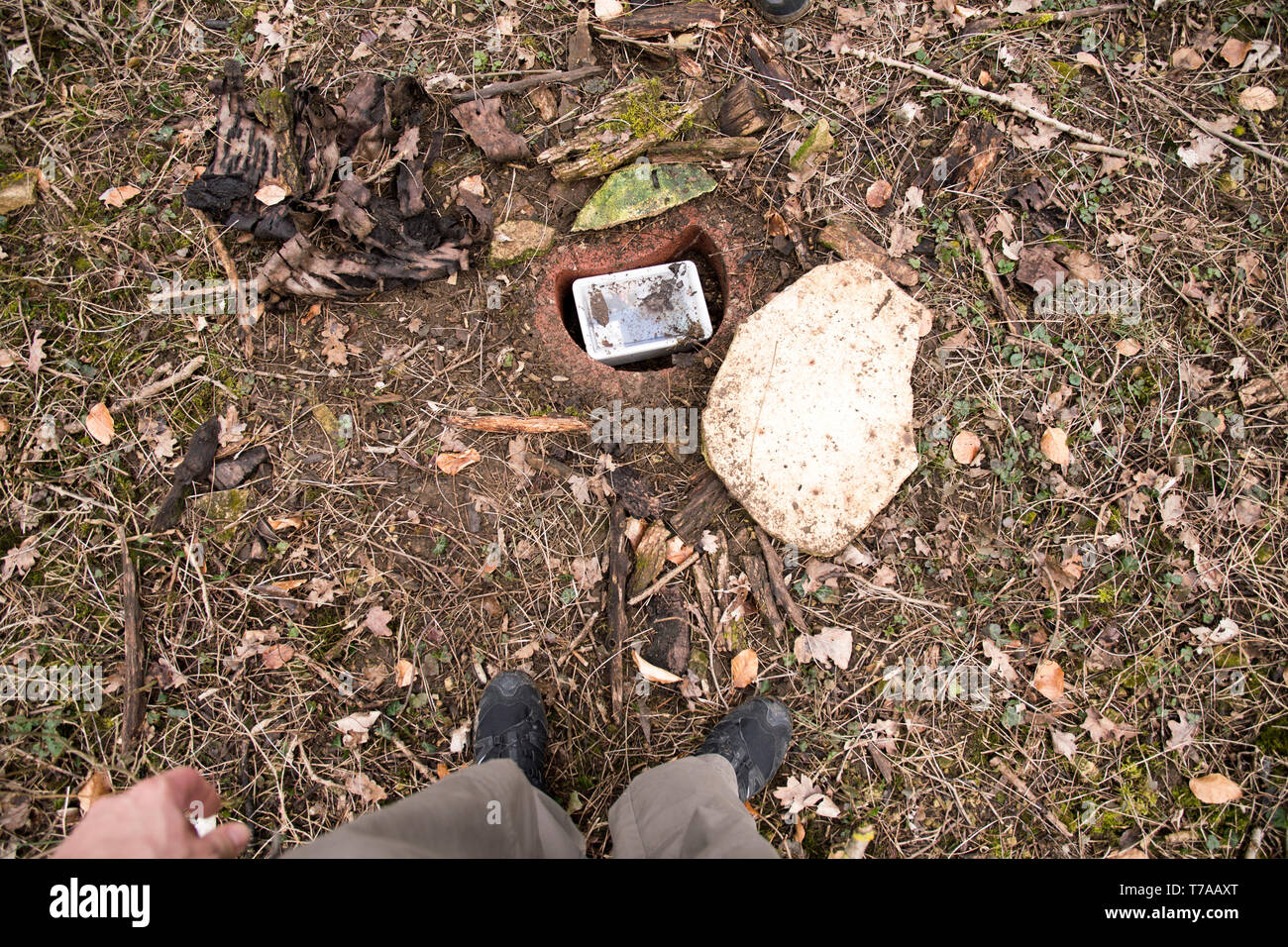 geocache hidden in the ground in a tube - Stock Image