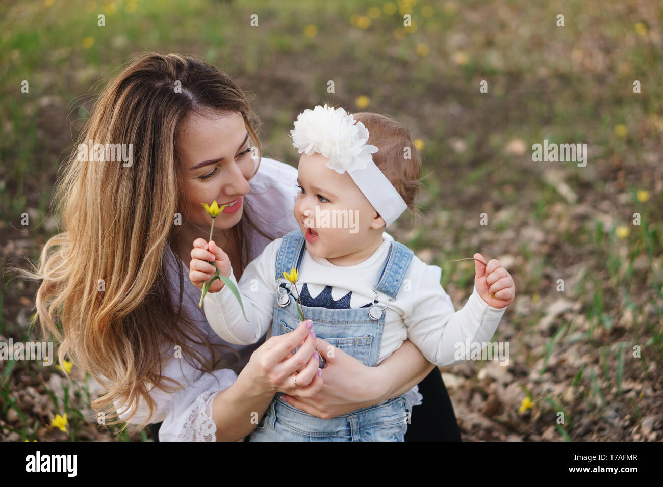 Young attractive mother shows her one year old daughter forest tulips family portrait close up they hold one flower in their hands communicate and