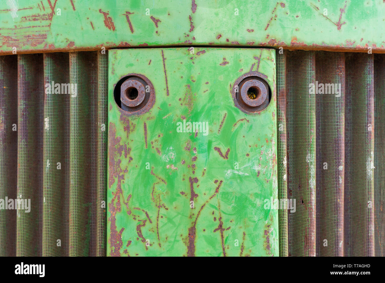 Front nose of farm equipment tractor. Metal background photo with rust, curvy metal vent and green chipping paint. - Stock Image