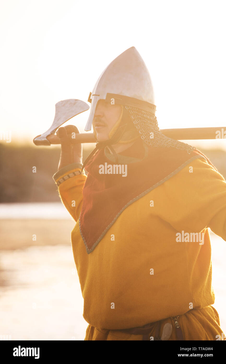 Portrait of slavic warrior reenactor with axe posing outdoors at seaside - Stock Image