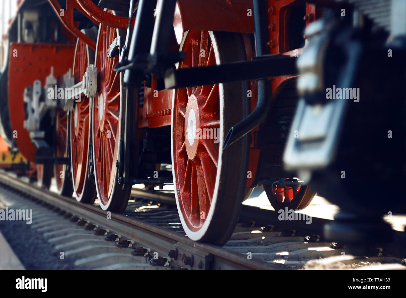 The red wheels of an old vintage steam locomotive, actively used in the 20th century, and now an exhibition model in the Museum. Stock Photo