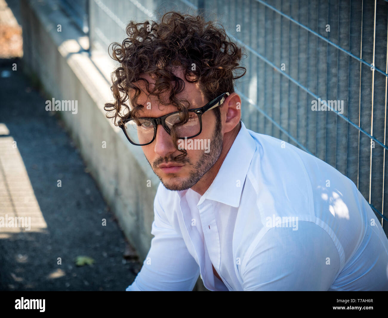 One handsome man in city setting wearing glasses Stock Photo