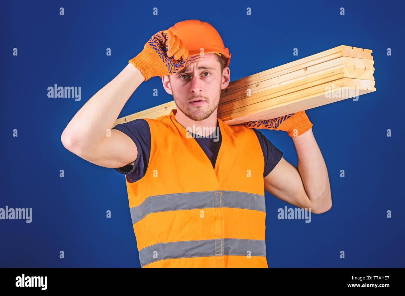 Carpenter, woodworker, labourer, builder carries wooden beam on shoulder. Woodworker concept. Man in protective gloves holds visor of helmet, corrects hard hat on head, blue background. Stock Photo