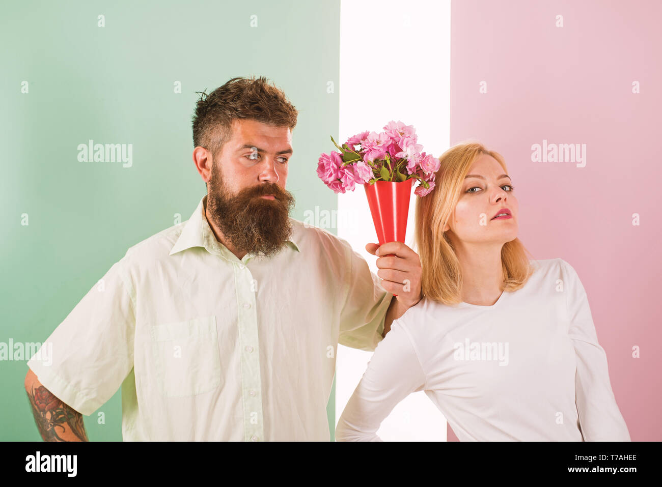 Hipster bearded give bouquet flowers girl excuse gesture. Man with beard apologyes woman. Couple date bouquet flowers gift. Apology concept. Couple in love problem relations forgive guilty boyfriend. - Stock Image