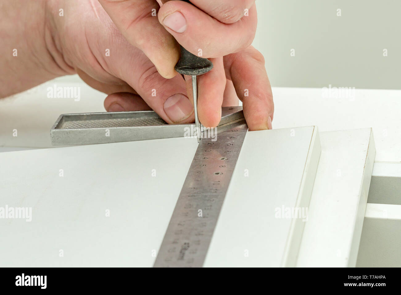 Assembly of furniture, makes holes with an awl - Stock Image