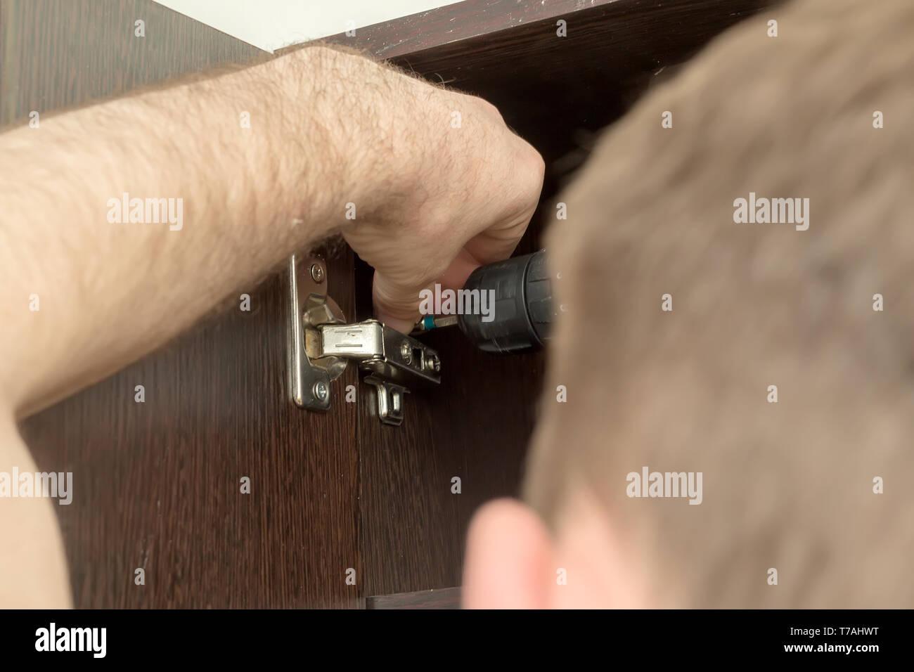 Fixing door furniture hinges. Fixing furniture hinges - Stock Image