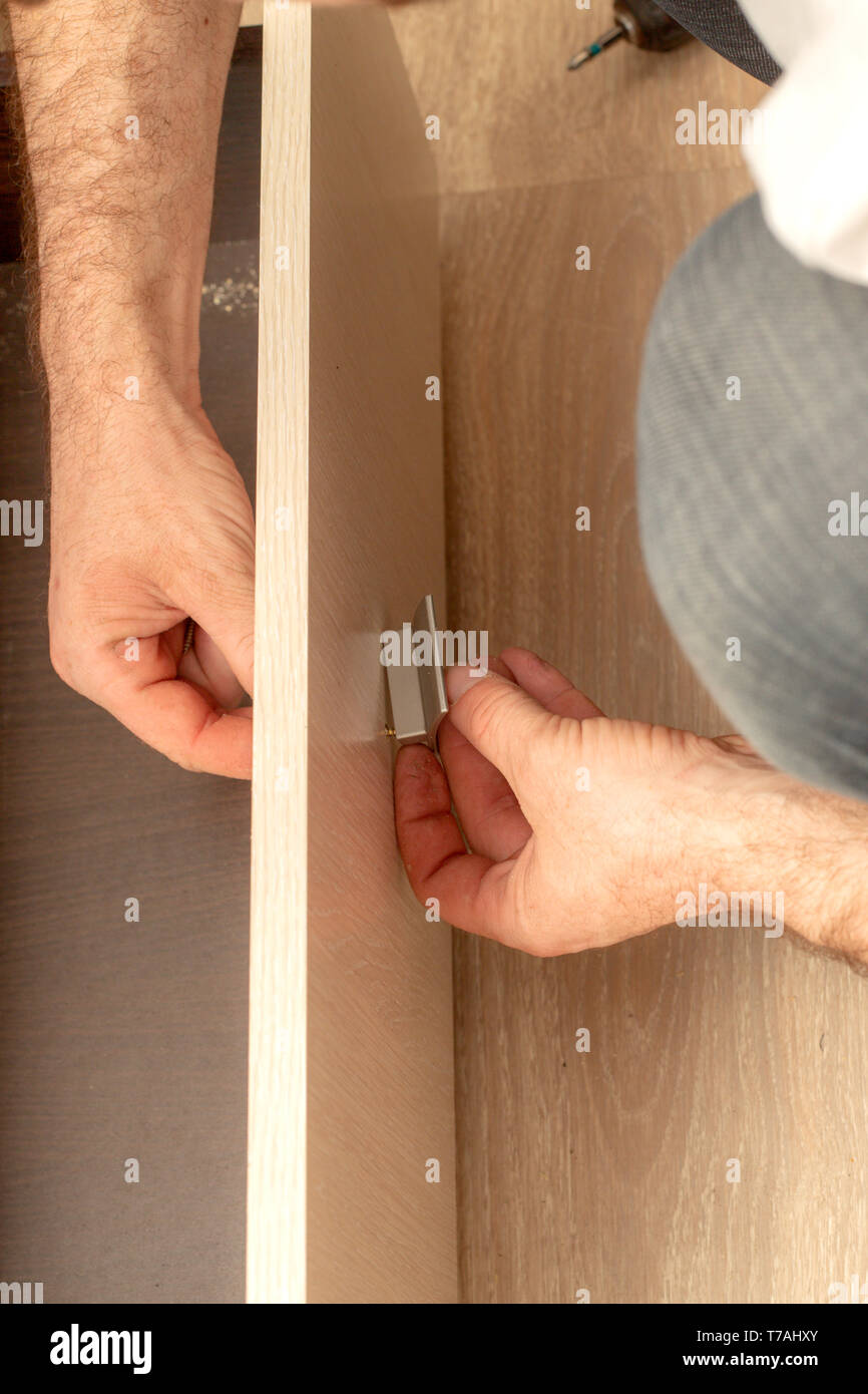 Installing door handles when assembling furniture. Close-up view - Stock Image