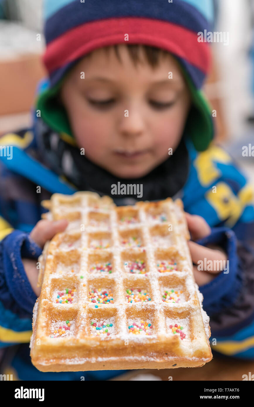 Little boy eating sweet waffle bought from a dessert stand in winter - Stock Image