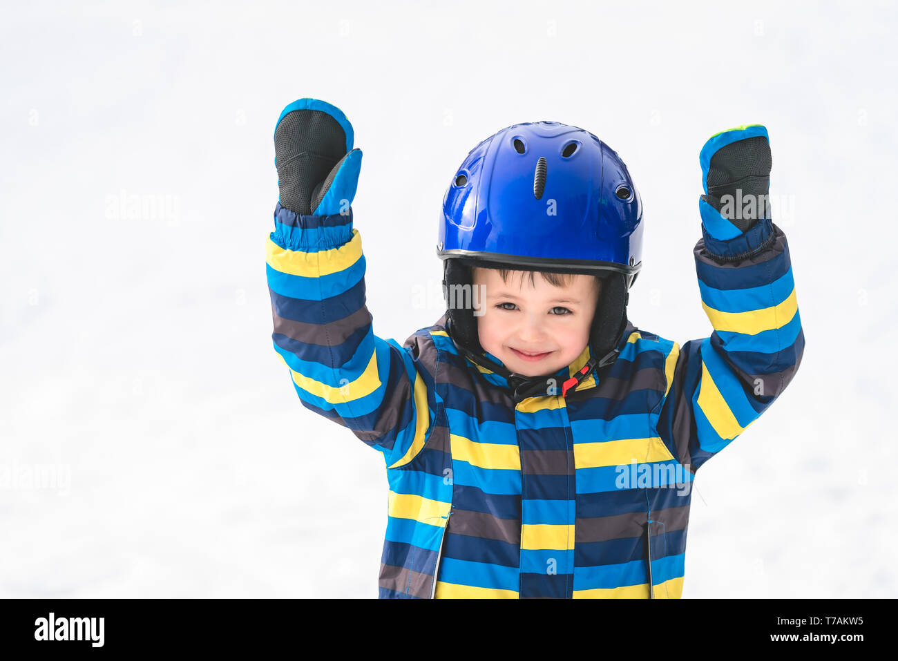 Winter portrait of a happy cute little Caucasian boy wearing ski helmet and throwing his hands up in the air after completing his first downhill ride - Stock Image
