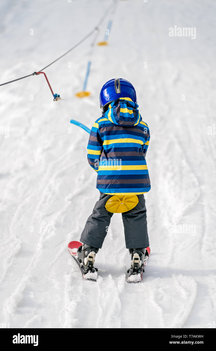 Little boy skier being pulled up the hill by a small round handheld ski lift - Stock Image