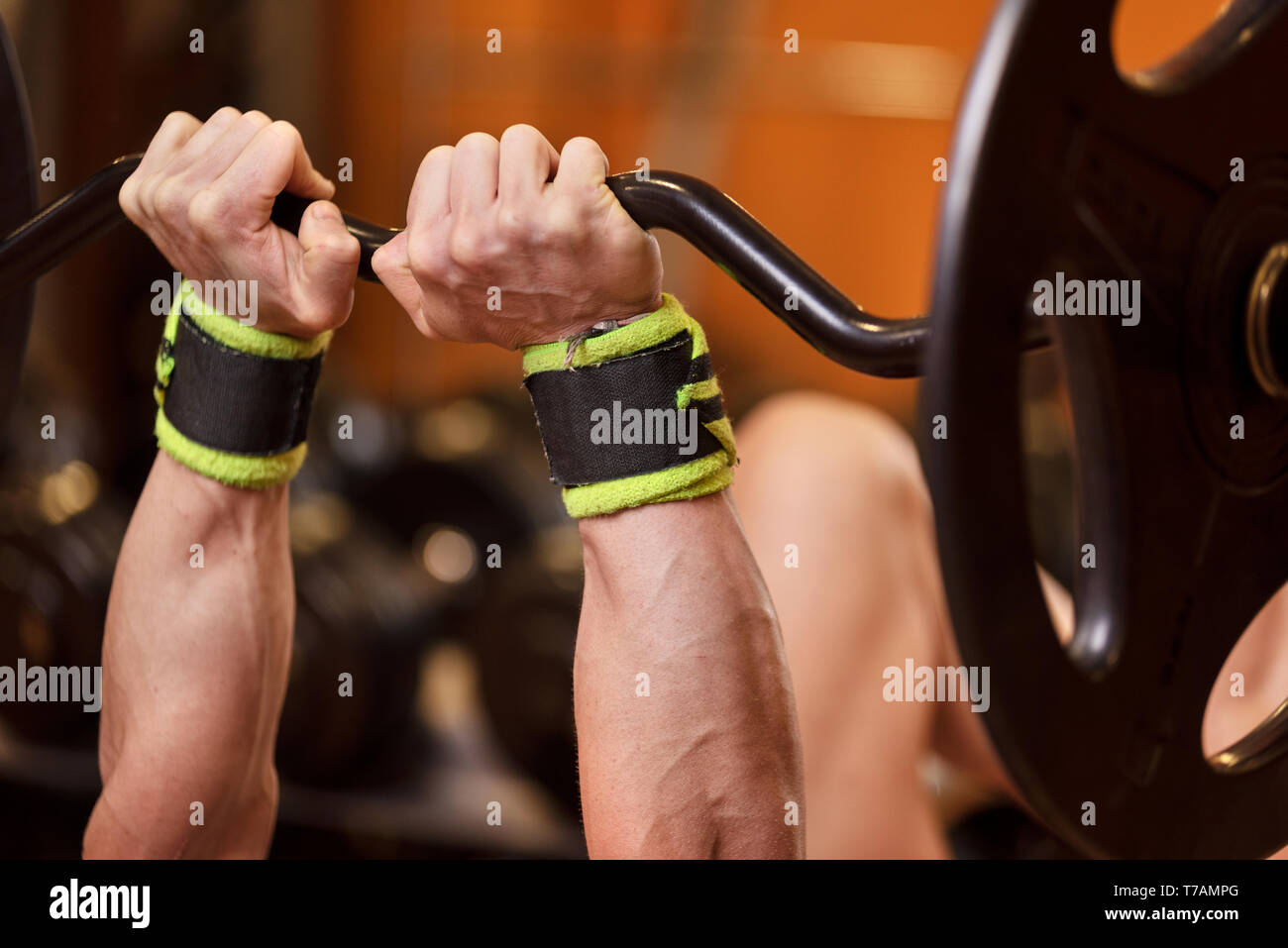 Handsome young muscular man close up, doing bench french press workout with barbell in gym . Stock Photo